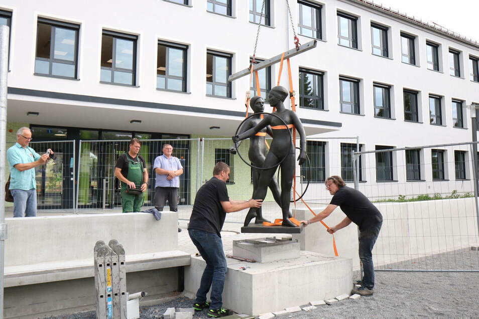 """Wieder komplett: Frank Hempel (li.) und Vinzenz Schmidt vom Unternehmen Ostmann + Hempel montieren die Skulptur """"Reifenspielende Mädchen"""" am alten Standort vor der Oberschule Am Merzdorfer Park. Die wird erst in den Sommerferien bezogen."""