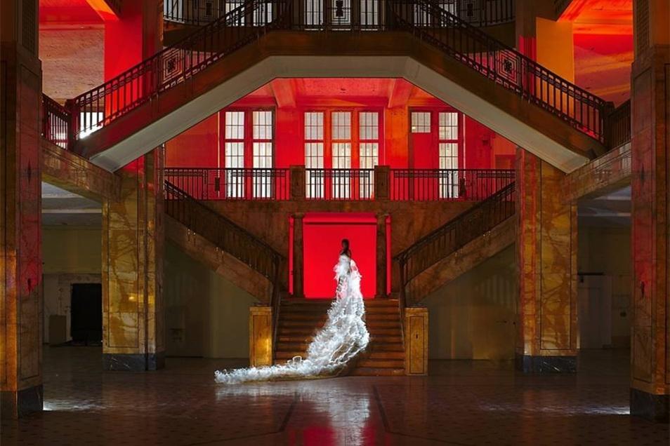 Oder im langen weißen Kleid die Treppe nach oben gehen.