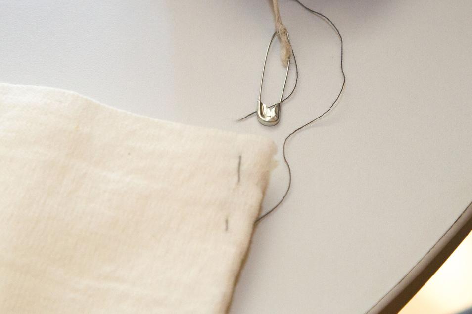 Die offene Seite auf der linken Stoffseite verschließen und von rechts eine Naht setzen, sodass ein Steg entsteht. Hier mit einer Sicherheitsnadel ein Band oder eine Schnur durchziehen. Dann die offenen langen Seiten zunähen.