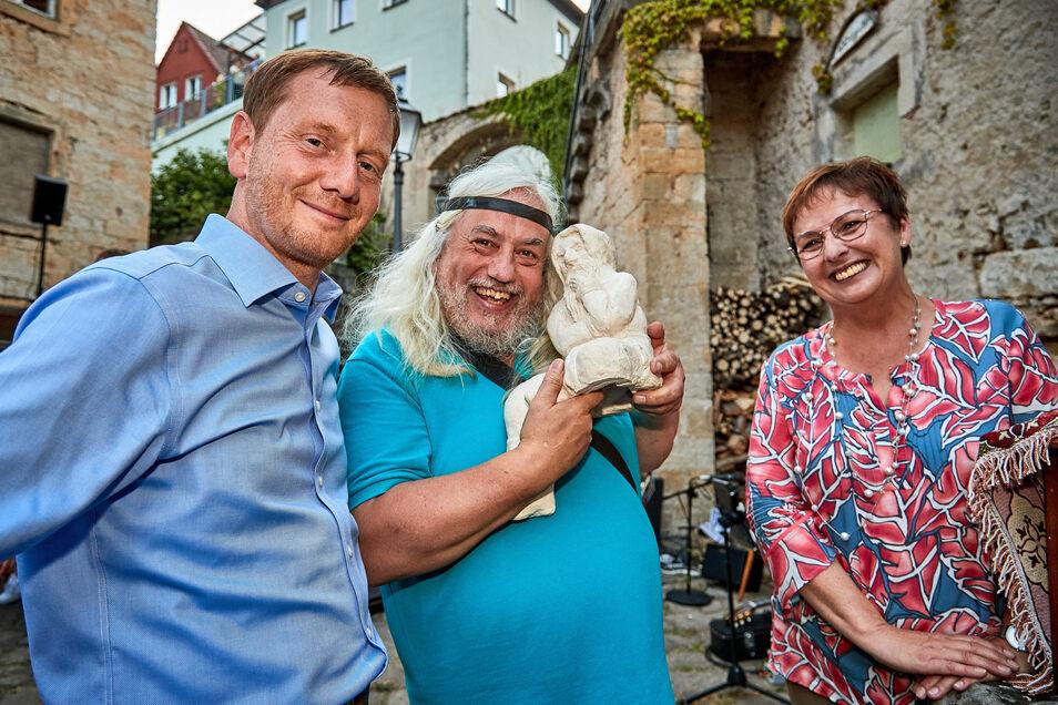 "Künstler Christian Hasse (m.) mit Querx ""Johannes"" Ministerpräsident Michael Kretschmer und MdB Patricia Lips (CDU)."