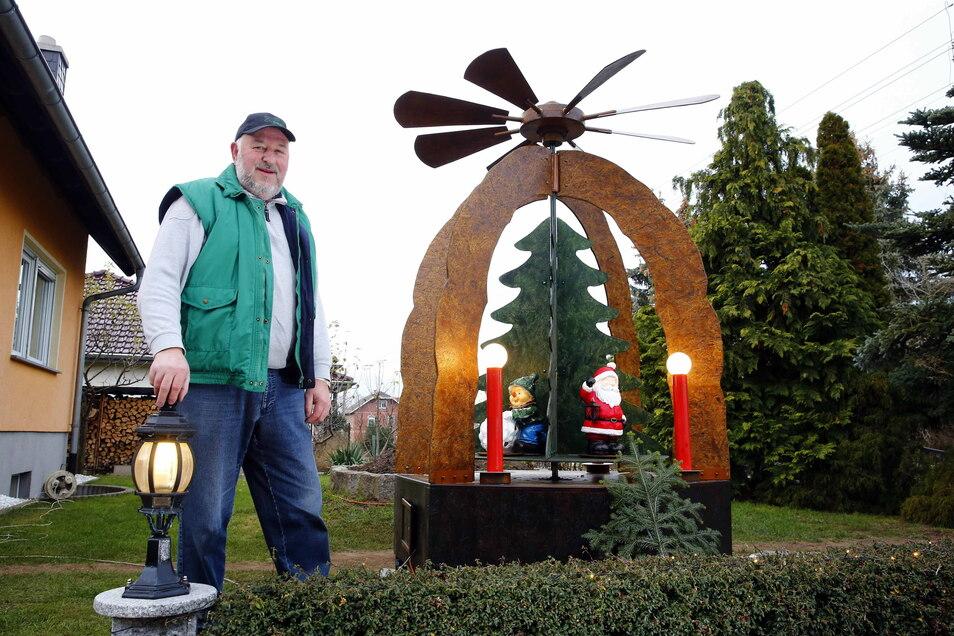 Tüftler Frank Richter neben seiner Riesenpyramide im Garten am Brackenweg in Schwepnitz. Noch bis ins neue Jahr soll sie sich drehen.