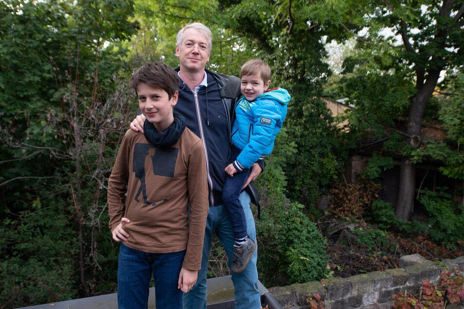 Conrad Föst genießt mit seinen Söhnen Adam (l.) und Hans von seinem Grundstück aus den Blick ins Grüne. Für das neue Baugebiet sollen alle Bäume hinter der Mauer gefällt werden.