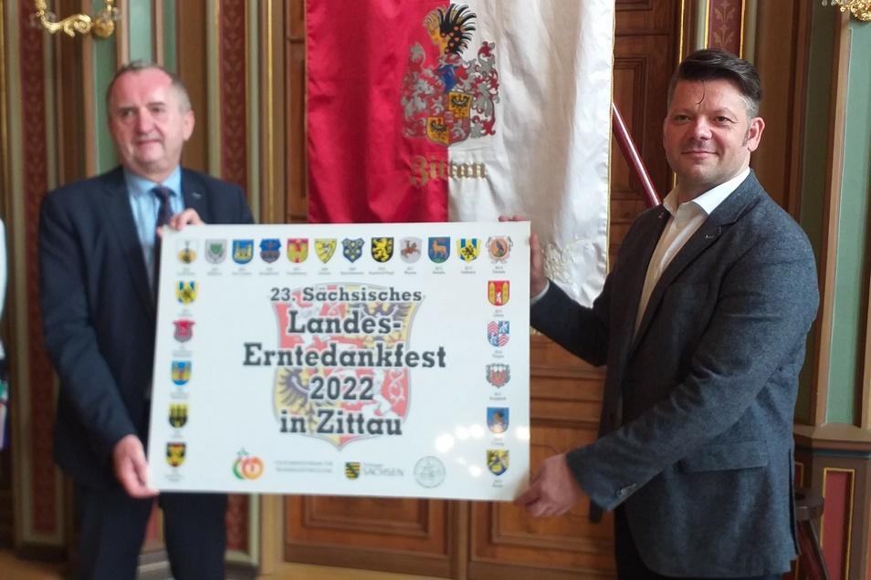 Staatsminister Thomas Schmidt (CDU, links) überreicht die Urkunde für das Landeserntedankfest 2022 an Zittaus OB Thomas Zenker (Zkm).