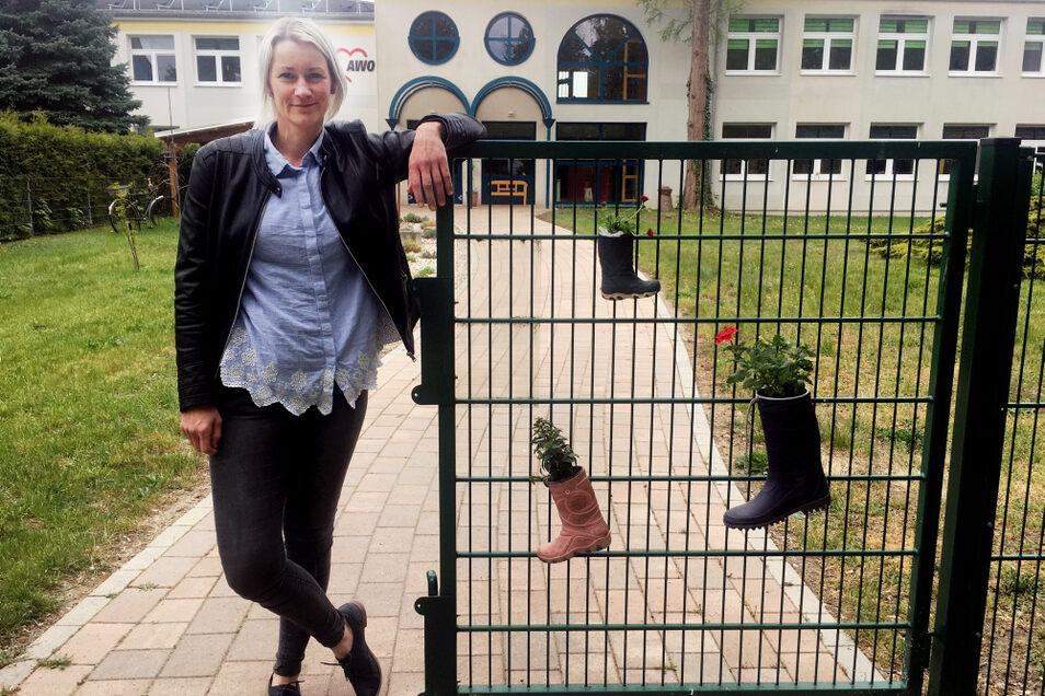 """Kati Ide, stellvertretende Leiterin der Kita """"Am Elsterbogen"""", am Eingangstor, das mit bepflanzten Gummistiefeln geziert ist."""
