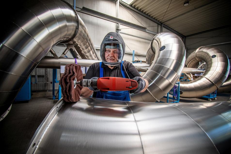 """Waldemar Tscherkaschin schützt sich in der Firma Atlantics bei Arbeiten an einer Rutsche mit einem ganz besonderen Helm. Der hat eine eingebaute """"Klimaanlage""""."""
