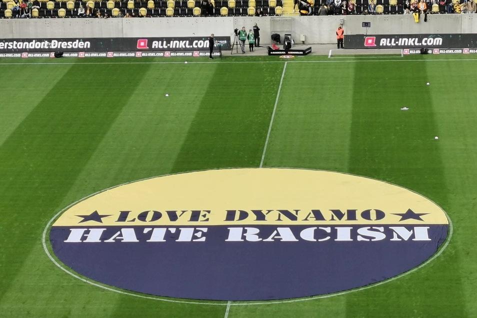 """Der Schriftzug """"Love Dynamo, hate Racism"""" ist auch auf einem großen Banner, das vor dem Spiel im Mittelkreis liegt, zu sehen."""