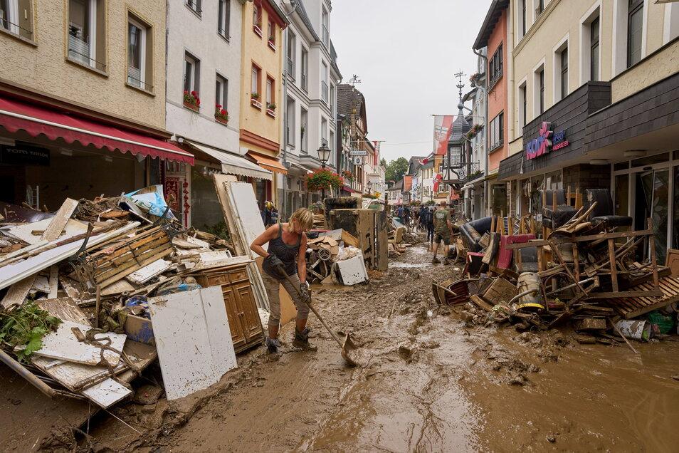 Anwohner und Ladeninhaber in Erftstadtversuchen, ihre Häuser vom Schlamm zu befreien und unbrauchbares Mobiliar nach draußen zu bringen.