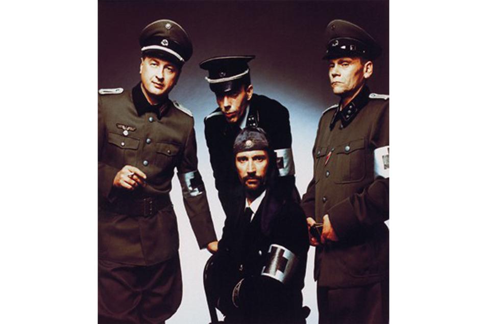 """Ein Pressefoto der Gruppe Laibach mit dem Titel """"Monumental Retro Avantgarde"""". Wegen ihrer Symbolik wurden sie in Westeuropa häufig als neonazistisch angesehen, in den USA dagegen eher als kommunistisch."""