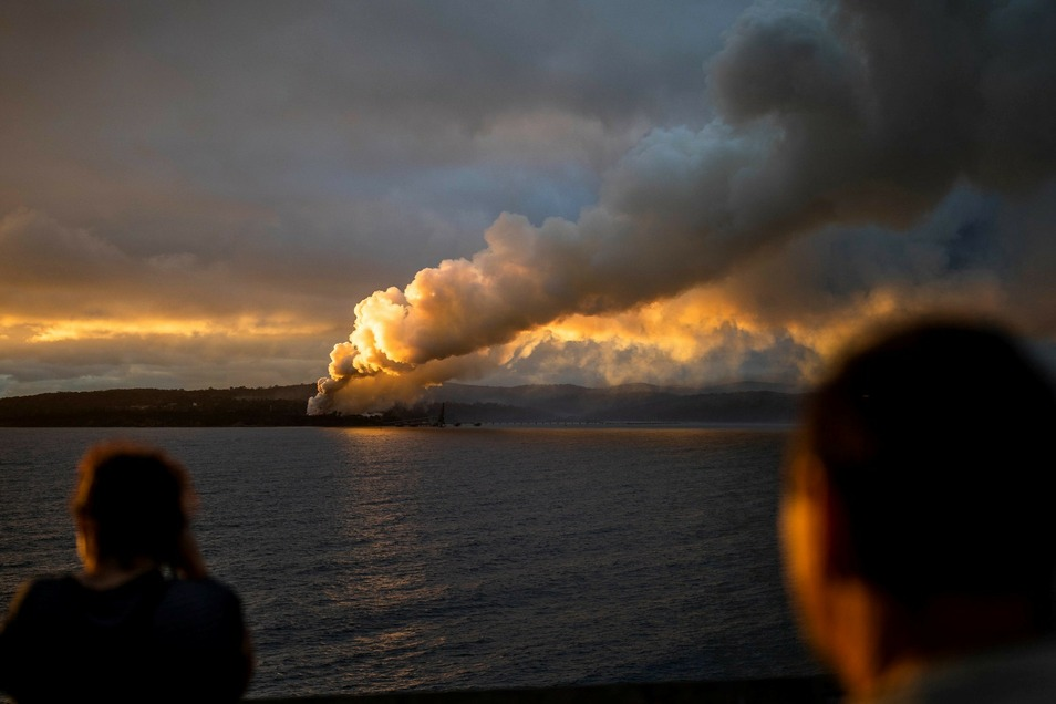 Menschen beobachten einen Brand. Seit Beginn der großen Buschfeuer verbrannten mehr als zehn Millionen Hektar Land. Mindestens 26 Menschen kamen ums Leben.
