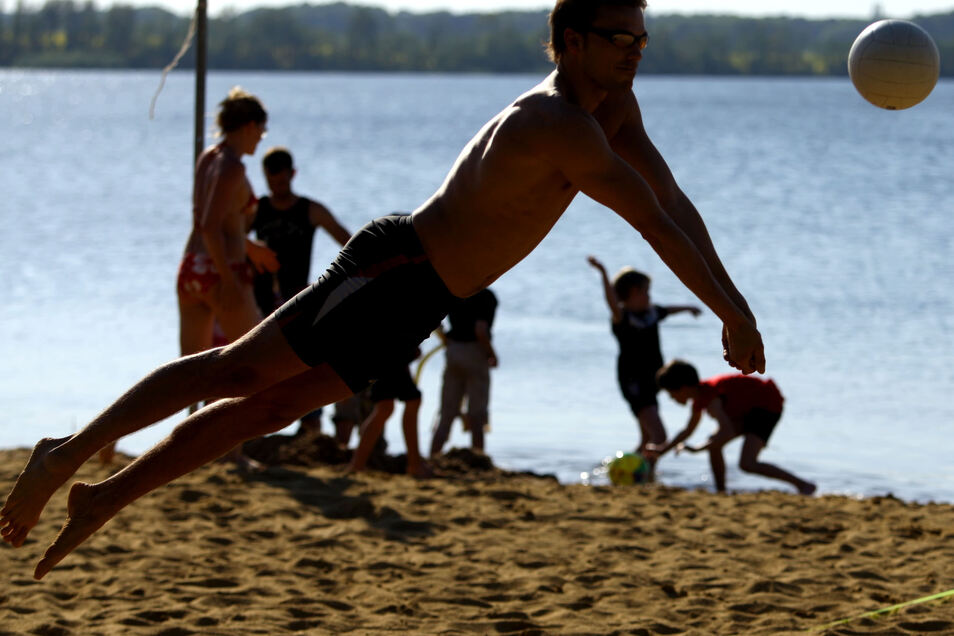 Ein junger Mann springt beim Beachvolleyball am Bautzener Stausee nach einem Ball.