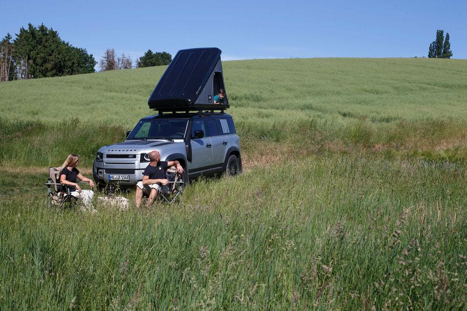 Das Zelt wird beim Land Rover Defender aus einer auf der Reling montierten Transportkiste gekurbelt.