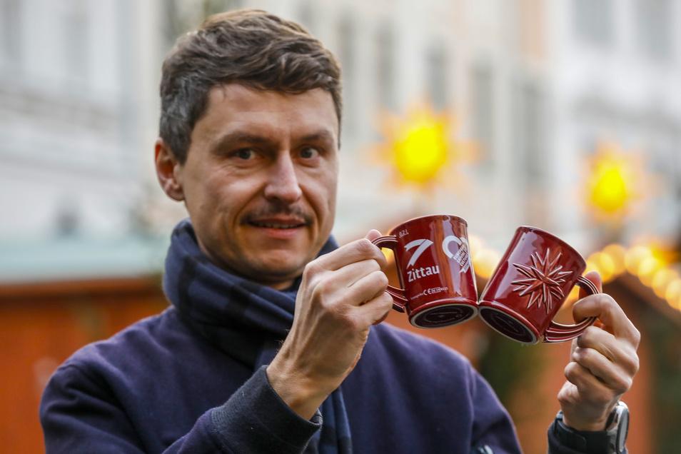 Kai Grebasch von der Stadt Zittau zeigt die neuen Glühweintassen für den Weihnachtsmarkt. Knapp 1.000 Stück hat sie geordert.