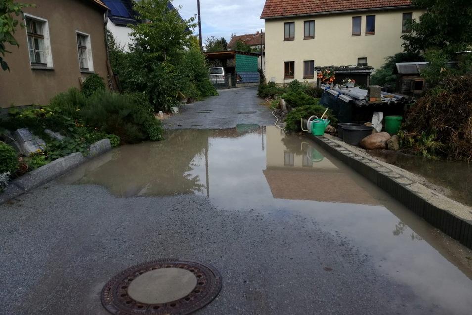 Bei Regen sammelt sich Wasser in einer Senke auf die Straße Am Steigerturm in Jenkwitz. Um die Stelle passieren zu können, gibt es nur zwei Möglichkeiten. Der eine führt über ein Privatgrundstück. Der andere funktioniert nur mit Gummistiefeln.