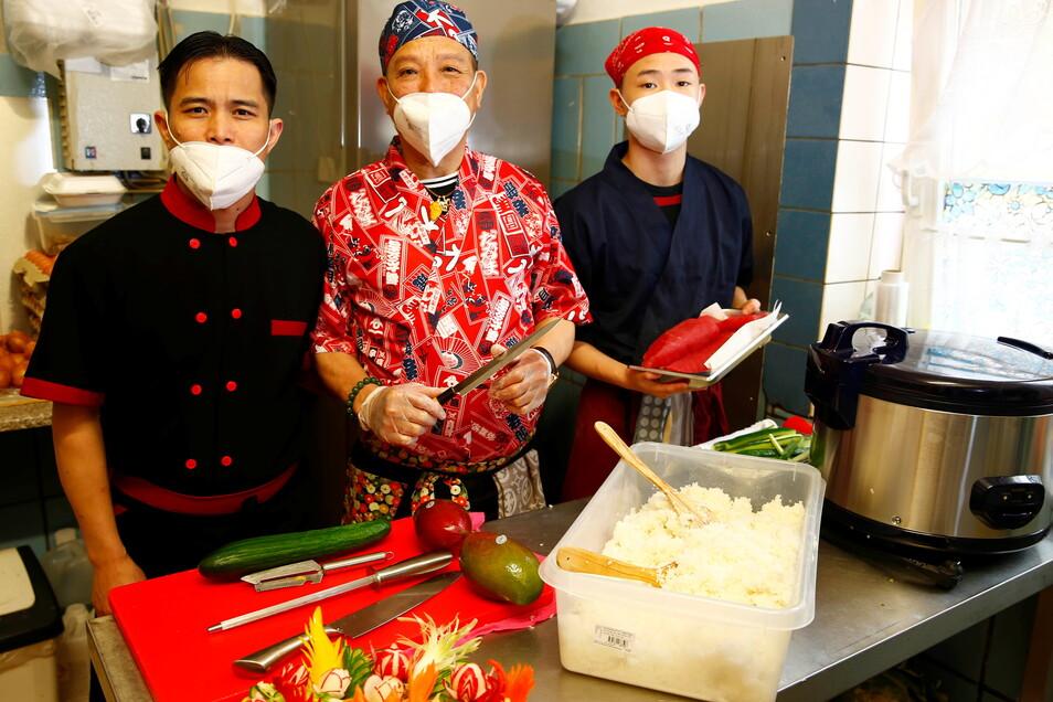 Bui Bao Quoc Trung (r.) geht bei seinem Vater (M.) in die Lehre , um auch ein guter Sushi-Koch zu werden. Imbiss-Betreiber Dam Quang Trung (l.) freut sich über die Verstärkung.