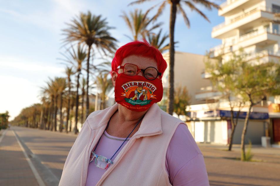 Heti Hartl steht mit einer Maske, die von einer der berühmtesten Bierkneipen (Bierkönig) gesponsored wird, am Strand El Arenal in Palma de Mallorca.