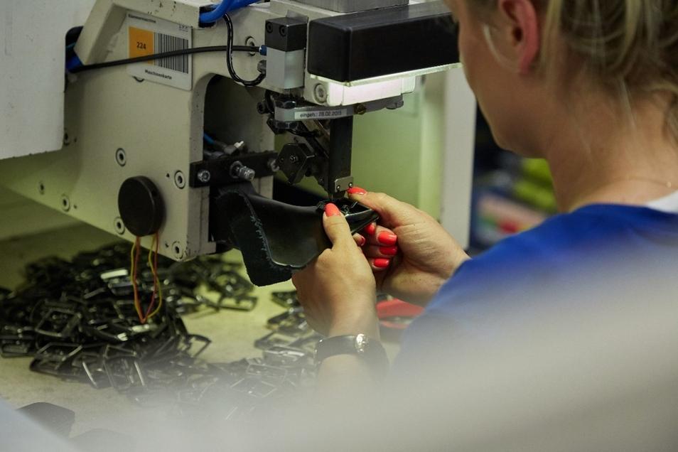 Die Schnallen müssen per Hand und mit maschineller Hilfe an den Leder- und Kunststoffriemen befestigt werden.