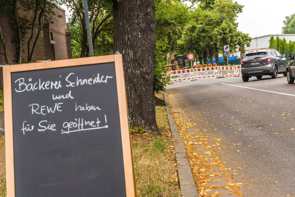 Ein handgeschriebener Hinweis an der Merzdorfer Straße macht Menschen darauf aufmerksam, dass trotz gesperrter Parkplatz-Zufahrt der Einkaufsmarkt und eine Bäckerei geöffnet haben.