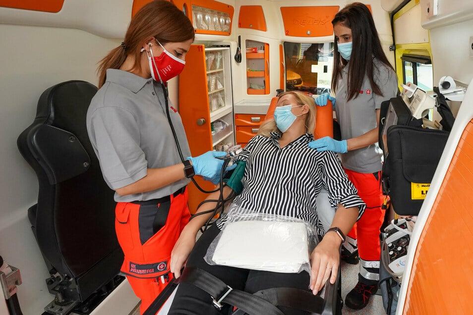 Die Rettungssanitäterinnen bei der Erstversorgung einer Patientin in einem Rettungswagen,