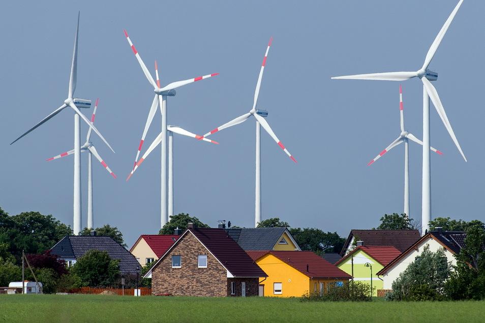 Dicht stehen die Windräder eines Windenergieparks an Einfamilienhäusern. Wie stehen die Parteien zu Wohnen und Klima?