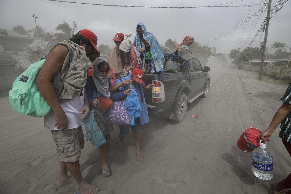Eine Familie steht auf einer mit Asche bedeckten Straße und bereitet sich während einer Evakuierung auf die Abfahrt aus dem von Vulkan Taal in der südlichen Provinz Cavite bedrohten Gebietes vor.