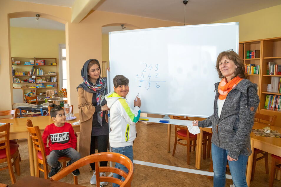 Sajad (links) staunt, was sein großer Bruder Jawad rechnen kann. Ihre Mutter Sofia Abdullahi ist stolz auf ihren großen Sohn, der gerne lernt. Heike Gelke (rechts) unterstützt die Familie bei Behördendingen.