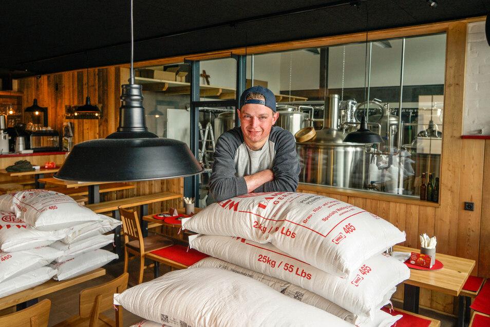 Im Gastraum des Brauhauses stapeln sich zurzeit Malzsäcke, weil im Lager Platz für Bauarbeiten gebraucht wurde. Während die Braukessel außer Betrieb sind, organisiert Braumeister Vincent Ebert die Flaschenabfüllung seines Zippl-Bieres.