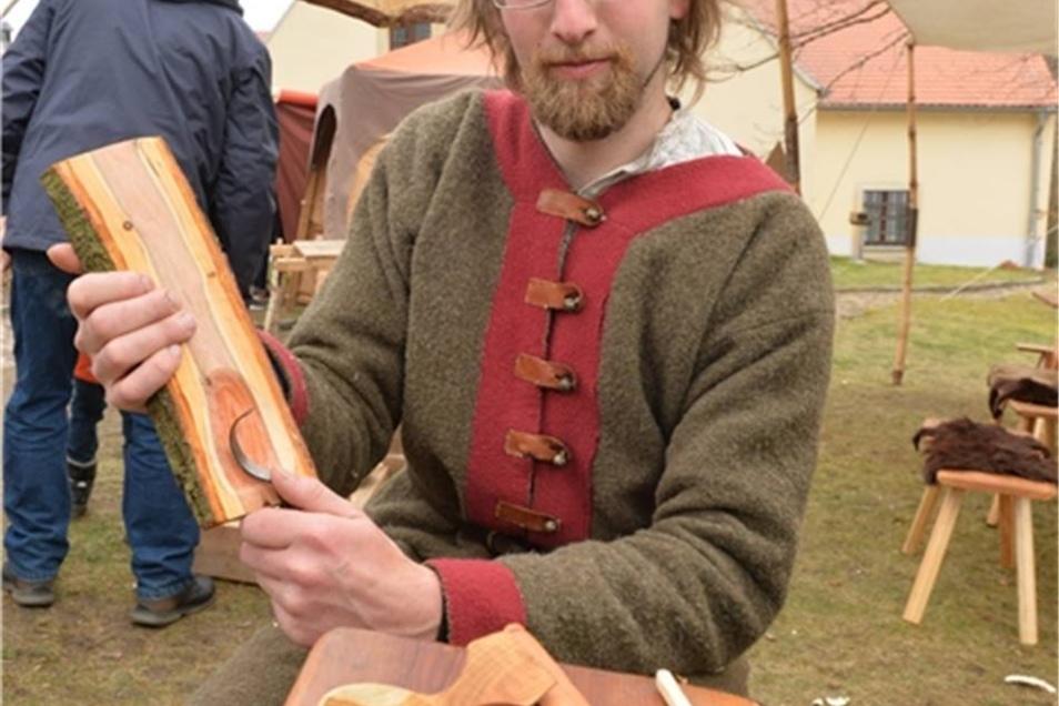 Sebastian Stock aus Tharandt bearbeitet ein Stück Pflaumenholz. Er zeigt das Handwerk des Löffelschnitzens.