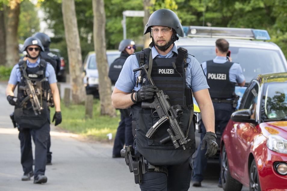 Schwer bewaffnete Polizisten sichern nach einer Schießerei ein Wohngebiet in Darmstadt