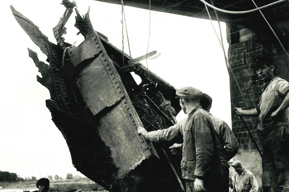 Das Foto aus dem Bestand des Riesaer Stadtmuseums zeigt Bergungsarbeiten an der gesprengten Elbebrücke im Mai 1945. Während die schwer beschädigte Bahnbrücke bis zum Juli 1945 wieder in Betrieb genommen werden konnte, dauerte es elf Jahre, bis Riesa eine