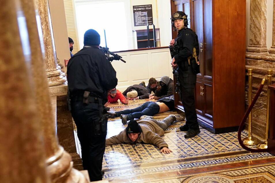 Die US-Kapitol-Polizei hält Demonstranten mit vorgehaltener Waffe fest.