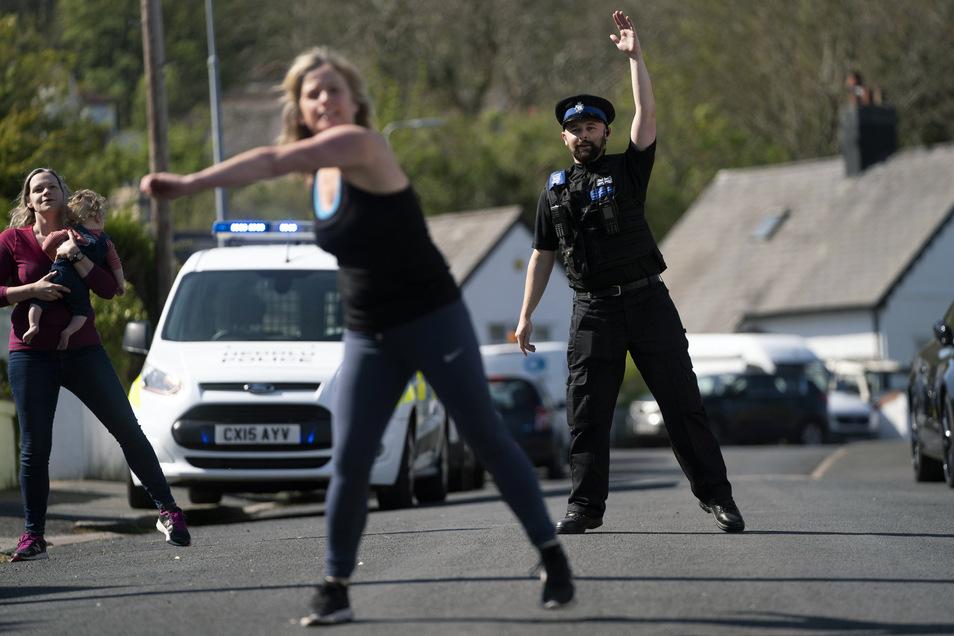 Großbritannien, Prestatyn: Ein Polizist nimmt an einer Tanzstunde teil, die von Anwohnern organisiert wurde. Ziel ist es, sich während des Coronavirus-Ausbruchs fit zu halten und sozialen Kontakt zu haben.