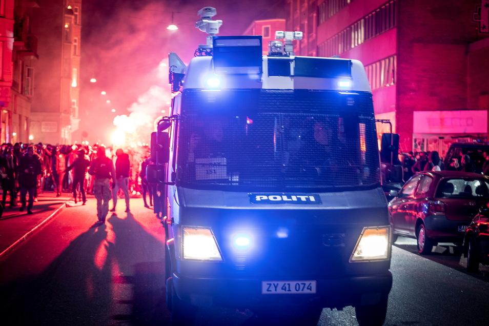 Ein Polizeifahrzeug steht mit Blaulicht vor Demonstranten gegen die Corona-Maßnahmen.