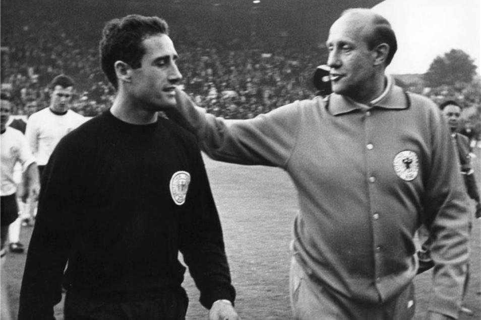 Bundestrainer Helmut Schön (r) gratuliert am 12. Juli 1966 beim Verlassen des Rasens des Sheffielder Hillsborough-Stadions seinen Torhüter Hans Tilkowski (l).