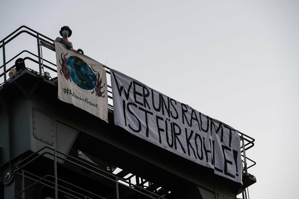 """Ein Demonstrant der Umweltschutz-Initiative """"Aufstand mit Abstand"""" steht auf einem der Türme auf dem Gelände des Heizkraftwerks Berlin-Moabit."""