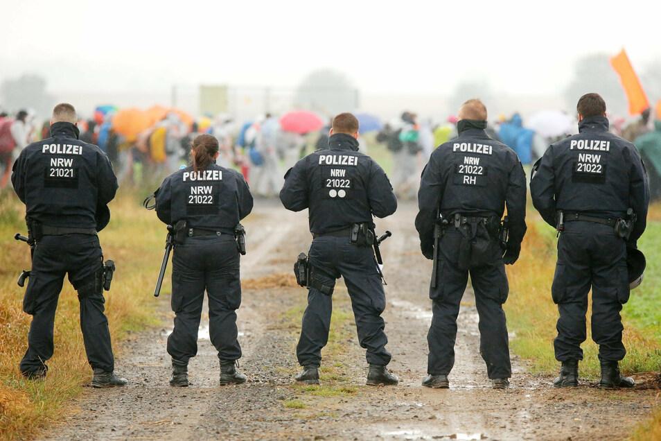Polizisten versperren einen Feldweg, während Aktivisten der Orangenen Finger mit ca. 150 Personen in Richtung Keyenberg marschieren.