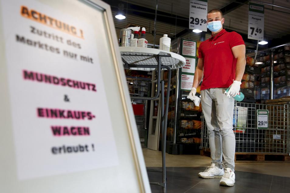 Im Hagebaumarkt in Großröhrsdorf desinfiziert Azubi Theo Schneider die Einkaufwagen.