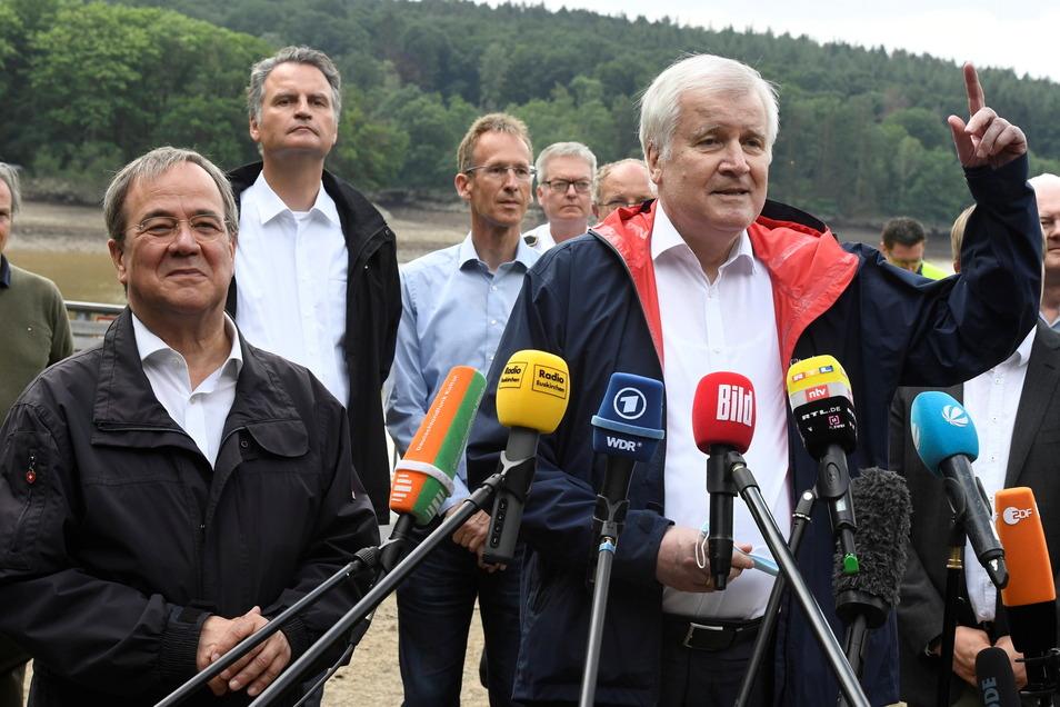 Bundesinnenminister Horst Seehofer (CSU, r) und der Ministerpräsident von Nordrhein-Westfalen, Armin Laschet (CDU, l) sprechen vor der Steinbachtalsperre zu den Medien. Die Dämme der Talsperre drohten wegen dem Hochwasser tagelang zu brechen.