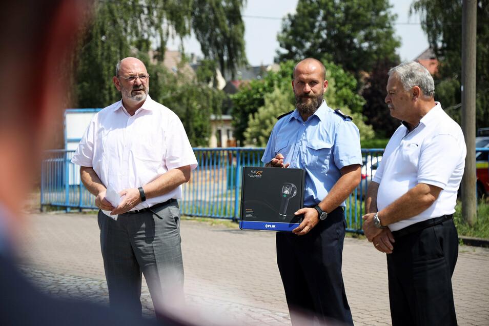 Drei Männer mit Präsent: Uwe Bartmann von der Sparkassen-Versicherung Sachsen, Gemeindewehrleiter Boris Krause und Bürgermeister Lothar Herklotz (v.l.n.r.).