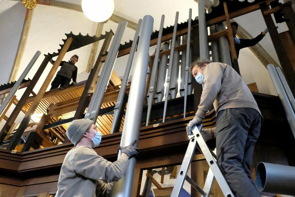 Die Orgelbauer balancieren die Orgelpfeifen behutsam auf den Prospekt. Die längste Pfeife ist 4,80 Meter.