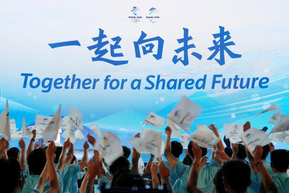 Menschen schwenken kleine Fahnen bei der Enthüllungszeremonie des offiziellen Mottos für die Olympischen und Paralympischen Winterspiele 2022 in Peking.