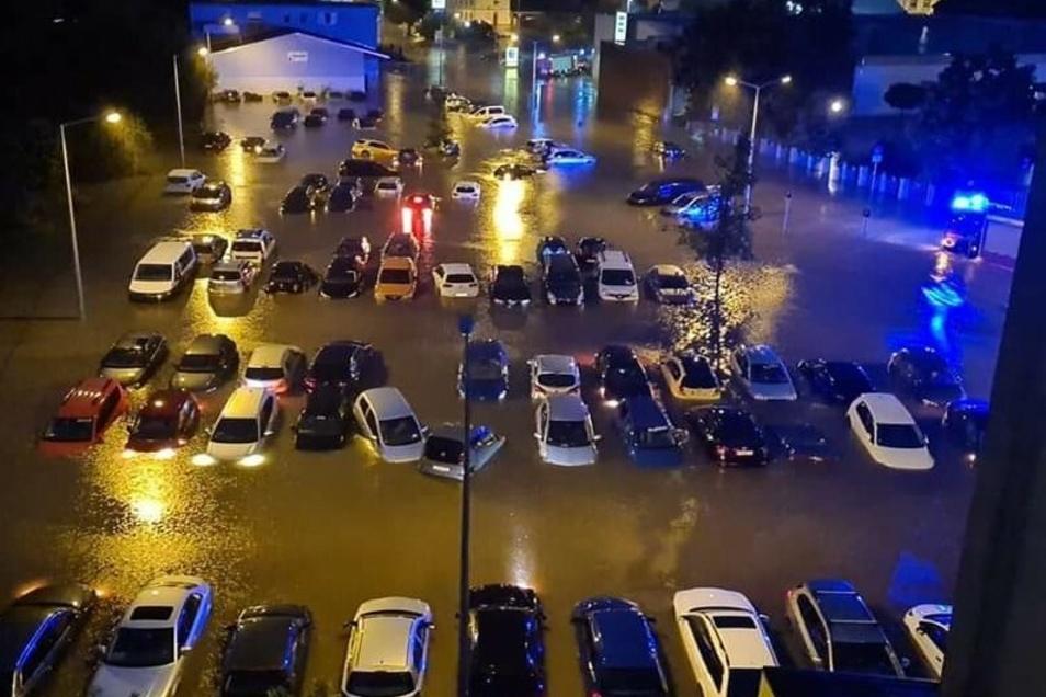 Autos stehen auf einem überfluteten Parkplatz.