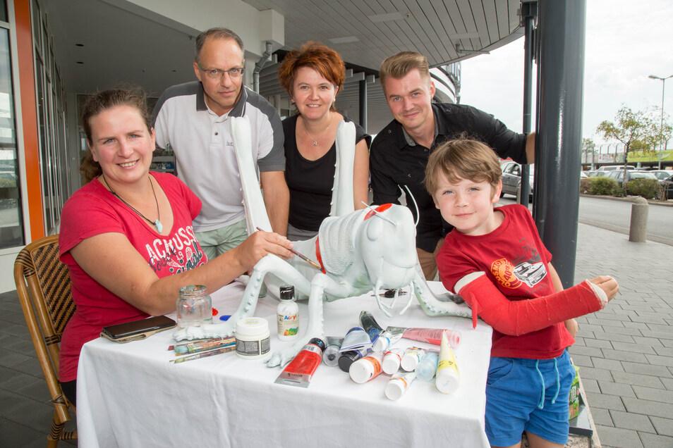Susanne Mühle aus Berlin bemalt unter den Augen von Michael Walter, Daniela Kiesewetter und Valentin Klepatzki eine Riesenheuschrecke. (von links). Ihr Sohn (rechts) ist kritischer Beobachter.