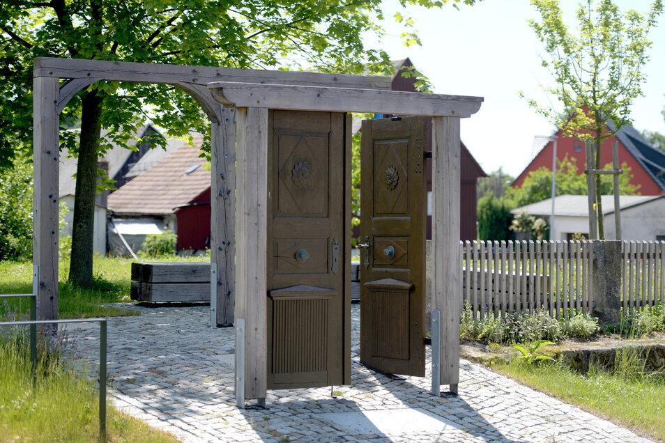 Auf die Umgebindebauweise hingewiesen wird ebenso am Rast- und Informationsplatz an der Hauptstraße im Ortsteil Oberseifersdorf. Die alte historische Tür hat einen besonderen Grund. Es ist die wieder aufgearbeitete Eingangstür des 1990 an dieser Stelle ab