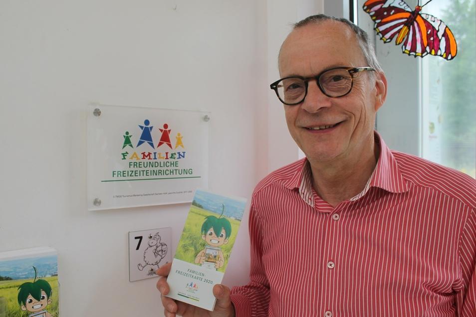 """Frithjof Helle, Geschäftsführer des Jonsdorfer Schmetterlingshauses, vor dem Schild, das sein Haus als """"Familienfreundliche Freizeiteinrichtung"""" ausweist."""