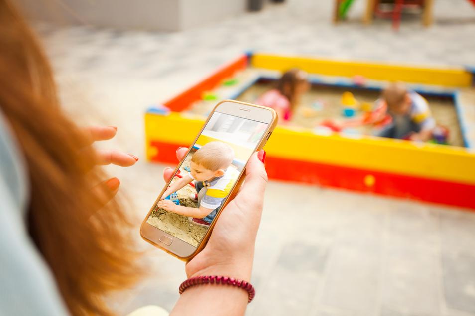 """Ständig macht es """"Pling"""". Das Handy lenkt Eltern auf dem Spielplatz ab. Rituale können helfen."""