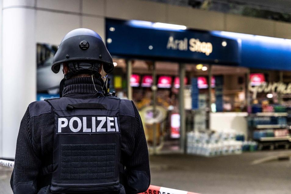 Ein Polizist sichert am frühen Morgen den Tatort, eine Tankstelle in Idar-Oberstein.