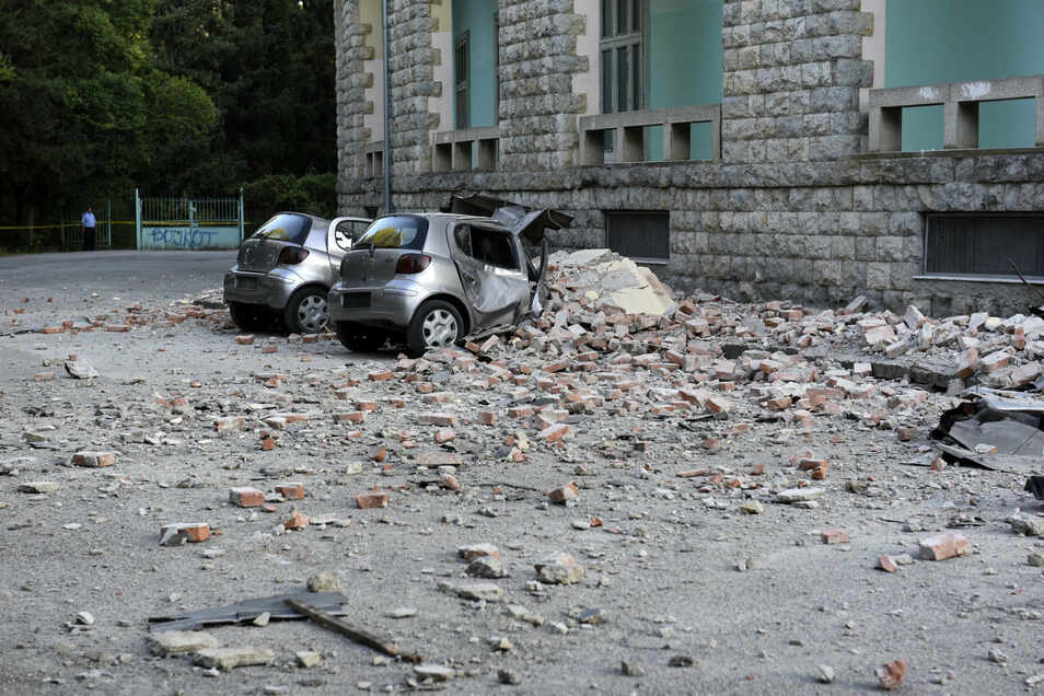 Zwei beschädigte Autos liegen nach einem Erdbeben unter den Trümmern vor dem Gebäude der Geologie-Fakultä in Tirana.
