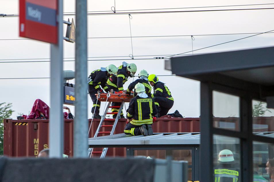 Einer der beiden verunfallten Jugendlichen wird durch Einsatzkräfte der Feuerwehr der Stadt Niesky von dem Waggon geborgen.