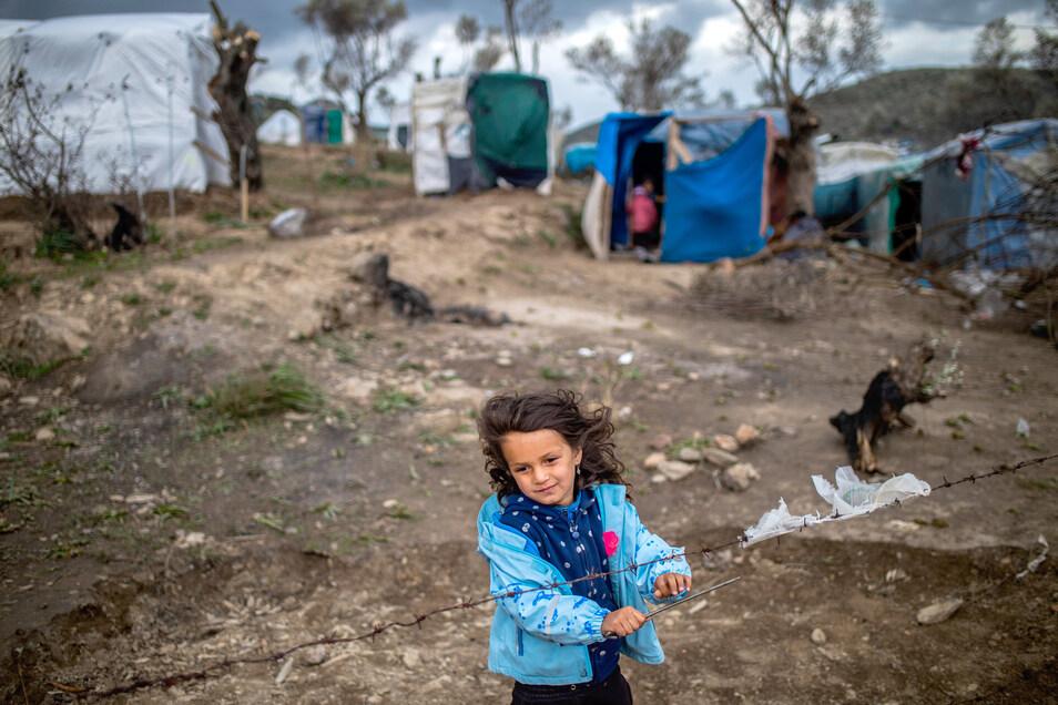 Ein kleines Mädchen steht am Stacheldrahtzaun in einem provisorischen Zeltlager auf Lesbos.