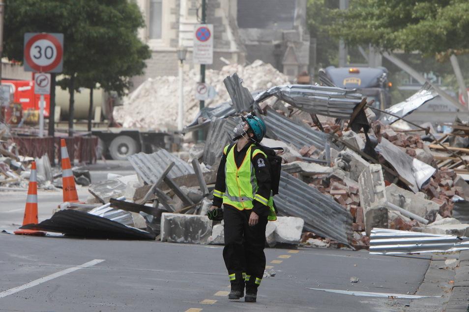 Am 2. März 2021 geht in Christchurch ein Mitarbeiter von Urban Search and Rescue durch das von einem Erdbeben zerstörte zentrale Geschäftsviertel.